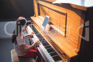 High angle view of concentrated girl practicing piano
