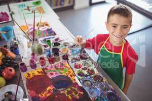 High angle portrait of boy painting at desk