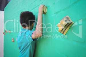 Side view of boy climbing wall