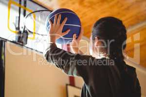 Side view of young woman practicing basketball in court