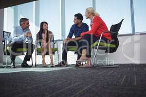 Business colleagues communicating while sitting on chairs at office