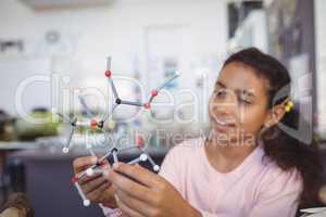 Elementary student holding molecule model