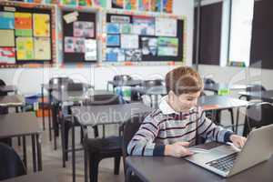 Schoolboy using laptop and mobile phone on desk
