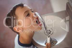 High angle view of boy drinking water from faucet