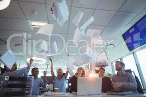 Cheerful business people tossing papers against ceiling