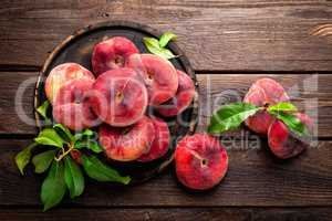 Peach, saturn or donut peaches with leaves