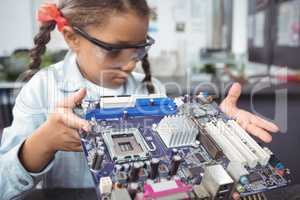 Elementary schoolgirl examining circuit board at electronics lab