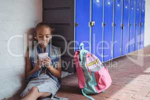 Elementary student listening music through headphones while using mobile phone