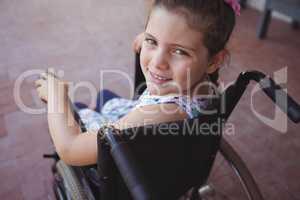 High angle portrait of schoolgirl sitting on wheelchair