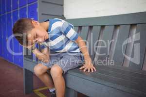 Thoughtful elementary boy sitting on bench