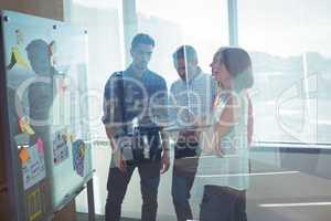 Business entrepreneurs standing by whiteboard seen through glass