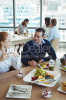 Young business colleagues talking at breakfast table