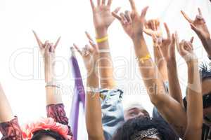 Fans gesturing horn sign with arms raised at music festival