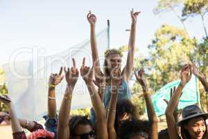 Happy woman with arms raised enjoying at music festival