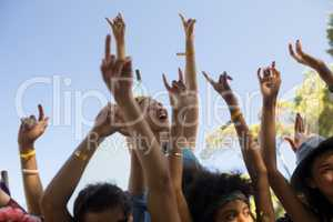 Cheerful woman with arms raised enjoying at music festival