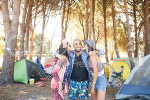 Females kissing male friends standing at campsite
