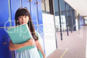 Portrait of elementary girl holding books in corridor