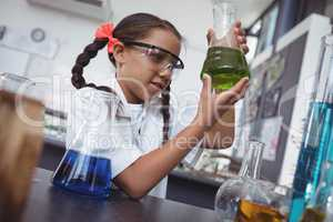 Elementary student examining green chemical in flask at laboratory