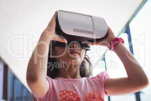 Low angle view of girl using virtual reality glasses against ceiling