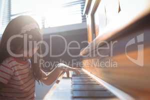 Elementary girl practicing piano in class