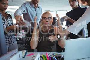 Irritated businesswoman sitting amidst team holding technologies