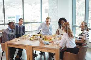 Business people discussing while sitting around breakfast table