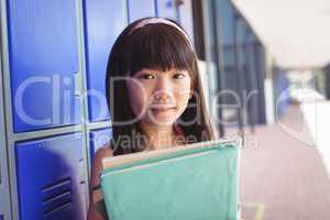 Portrait of elementary schoolgirl holding books in corridor
