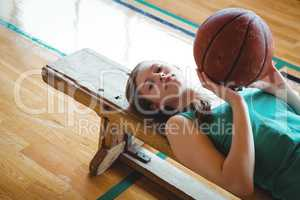 Portrait of woman with basketball lying on bench in court
