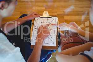 Coach explaining diagram to female basketball player