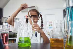 Elementary student doing experiment with chemical at laboratory