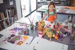 High angle view of concentrated girl painting at desk