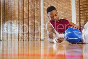 Male basketball player using mobile phone