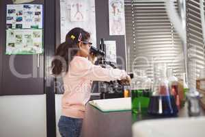 Side view of elementary schoolgirl using microscope at laboratory
