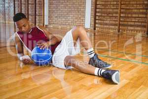 Full length of male basketball player using mobile phone