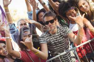 Happy young man gesturing shaka signs with friends at music festival