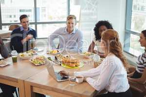 Business colleagues discussing while sitting around breakfast table