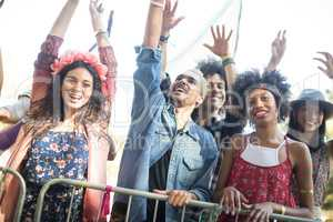 Happy friends with arms raised enjoying during music festival