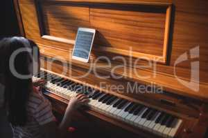 High angle view of girl wearing headphones while practicing piano in classroom