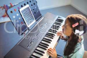 Elementary girl looking at digital tablet on stand while practicing piano