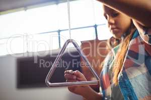 Low angle view of girl playing triangle
