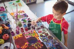 High angle view of boy painting at desk