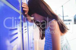 Side view of sad girl leaning on lockers