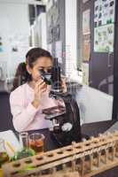 Elementary student looking through microscope at laboratory