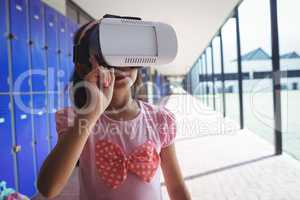 Elementary student using virtual reality glasses in corridor