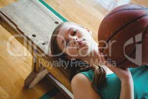 Portrait of female basketball player with ball lying on bench in court