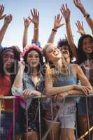 Happy female friends standing by railing at music festival