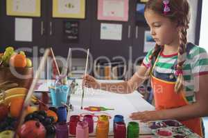 Concentrated girl painting at desk