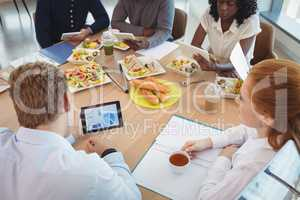 Businesswoman holding coffee cup while colleagues using digital tablets around breakfast table