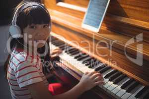 High angle portrait of girl wearing headphones while practicing piano