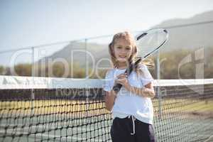 Smiling girl holding tennis racket while standing by net
